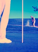 Golfer Swinging from the Bunker