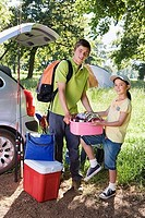 Teenage boy 15-17 and girl 8-10 unloading fishing equipment and coolbox from car boot, side view, portrait