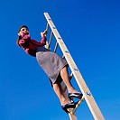Businesswoman with Cellular Phone on Ladder