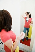Woman looking at herself in mirror (thumbnail)