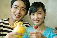 Young couple holding cocktails, clinking glasses