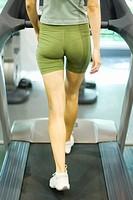 Woman walking on treadmill, rear view, waist down