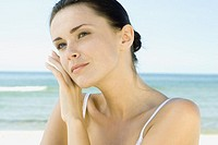 Woman touching face with back of hand, sea in background, head and shoulders