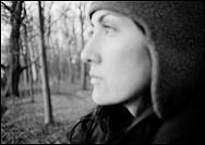 Profile on woman in winter hat standing in forest