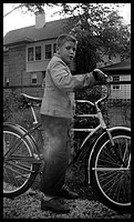 Boy with shiny bike looks at camera circa 1940