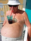 jElderly Man Sucking Drink Through a Straw From a Drink Sitting on His Stomach