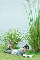 Young woman lying on grass near body of water, reading