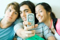 Teenage friends taking photo with cell phone, focus on phone in foreground (thumbnail)