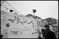 Mean walking down Pakistani street against backdrop of Arabic writing on wall of building