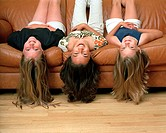 Three girls lying upside down on couch