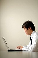 Profile of businessman working on laptop
