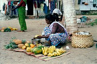 Indian woman sitting on ground selling fruit
