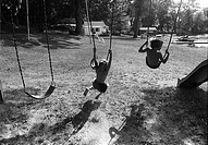 Young boys swing on swingset in swim trunks