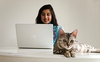 Woman using laptop computer, cat in foreground