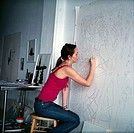 Woman on stool draws on large paper canvas