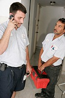 Hispanic male air conditioning repairman, thermostat, job, cell phone, tool box. Miami Beach. Florida. USA.