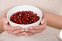 Woman holding bowl of pomegranate seeds