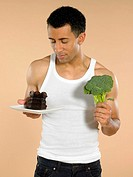 Man with chocolate cake and broccoli