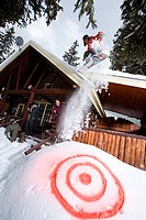 Man snowboarding off chalet roof