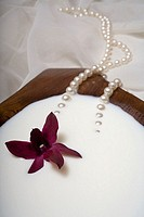 Spa elements, koa bowl filled with milk, garnished with an orchid and a pearl necklace