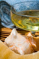 Spa elements, glass filled with yellow liquid, with seashell, towel and natural loofah