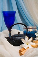 Spa elements, candle, flowers, kettle and glass nestled upon flowing cloth