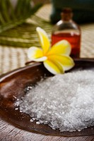 Spa elements, koa bowl filled with raw salt, plumeria, leaf and bath oil blurred in background