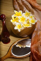 Spa elements, bright yellow plumerias in a koa bowl, hand mirror, scarf, lauhala mat and glass bottle