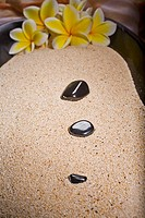 Spa elements, polished black rocks and plumerias in a bowl filled with sand
