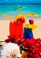 Tropical cocktails garnished with flowers and fruit on the beach