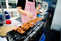 Thailand, Bangkok, Close-up of hands tending to chicken skewers cooking on grill