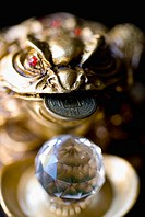 Close-up of a golden frog statue with an asian coin in it's mouth next to a prism