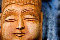 Close-up on the face of a wooden Buddha sculpture