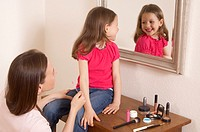 happy young girl wearing lipstick looking at herself in mirror