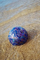 Art glass gloat in shallow ocean water on sandy beach