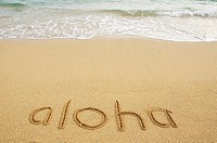 Aloha written in sand with wave