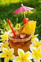 A mai tai garnished with fruit and flowers