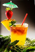 A mai tai garnished with pinapple and a strawberry