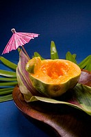 Studio shot of half of a papaya, seeds removed, with cocktail umbrella