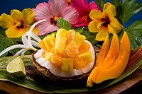 Studio shot of a variety of tropical fruit served on a ti leaf with flowers