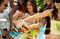 Young Friends Eating Hamburgers at Pool Party