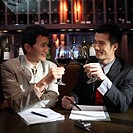 Two Businessmen Toasting in a Bar
