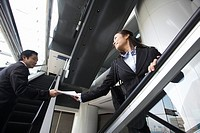 Businessman and Businesswoman on Escalators