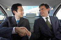 Two Businessmen Shaking Hands in Back Seat of Car
