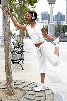 Young Woman with Headphones Stretching