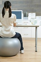 Woman sitting on an exercise ball at her desk