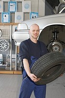 Friendly mechanic carrying tire