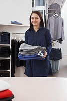 Store clerk carrying stack of folded pants