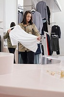 Woman looking at t-shirt in clothing store