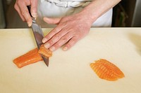Sushi chef cutting slices of fish